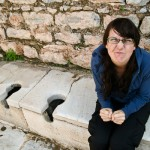 Laura on ancient public toilet at Ephesus.