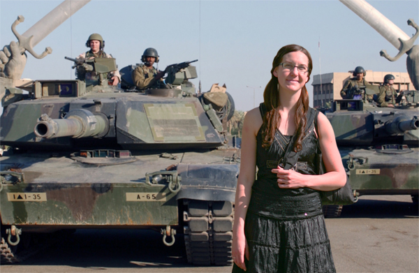Laura poses in front of some American forces, who were dismantling an IED about 50 feet up the street.