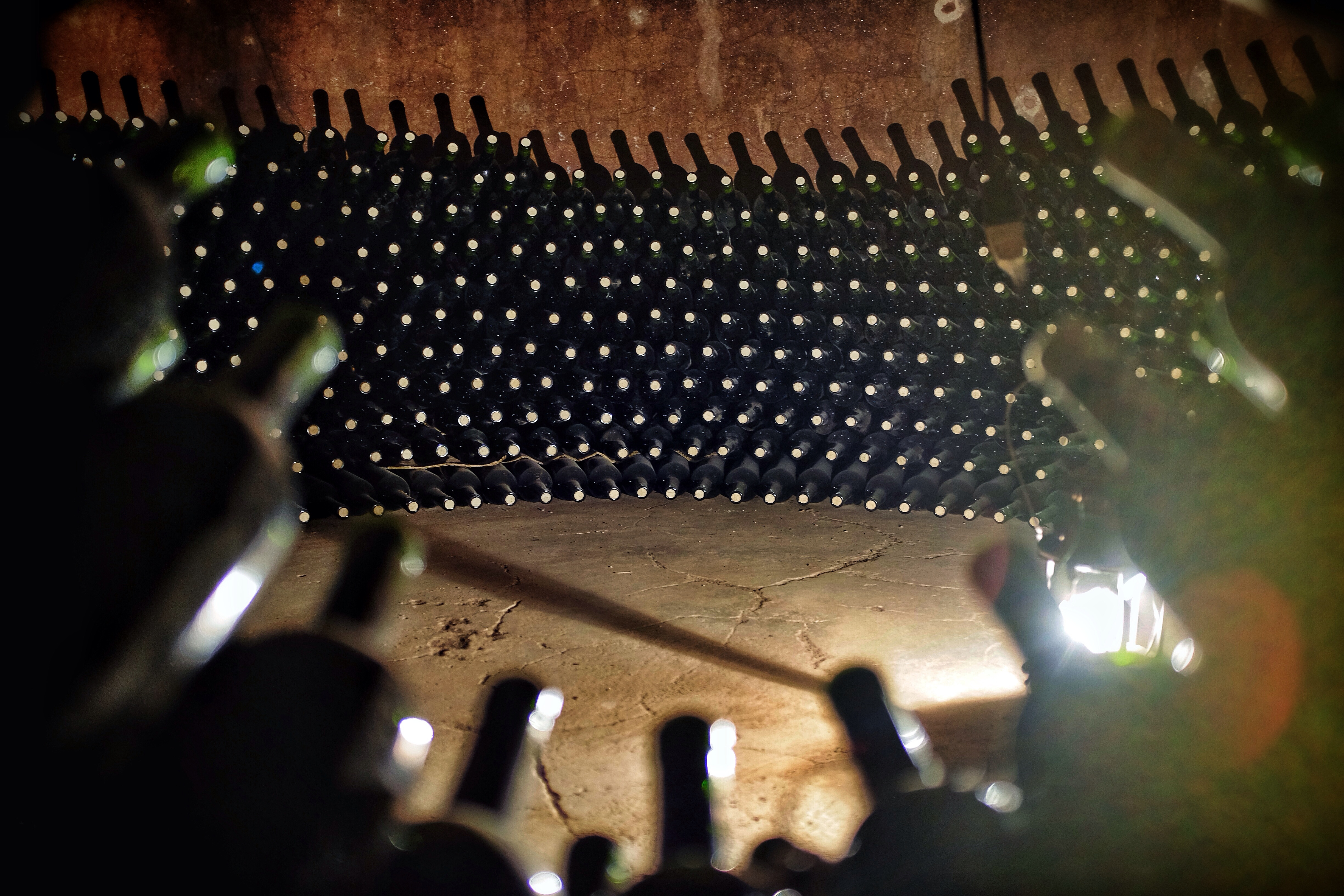 Bottles aging in the old vats of  the Famila di Tommaso bodega (winery).
