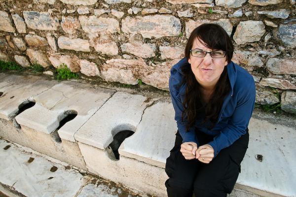 Laura on ancient public toilet at Ephesus.