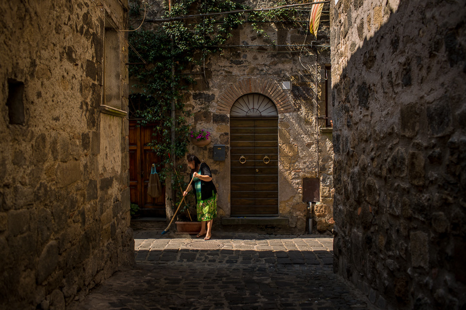 A woman sweeping up in Bolsena.